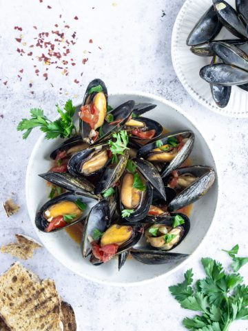 Top view of plate of cooked mussels in a white wine and tomato sauce