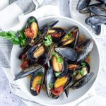 Plate of mussels sitting on a white napkin