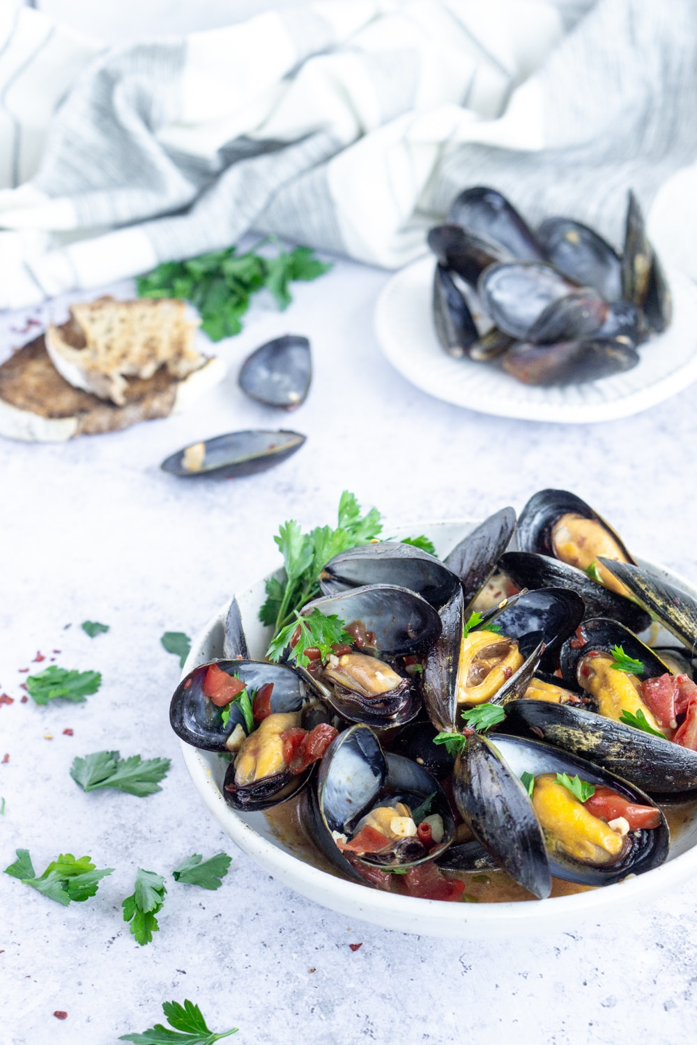 Side view of a bowl of mussels with mussel shells and bread in the background