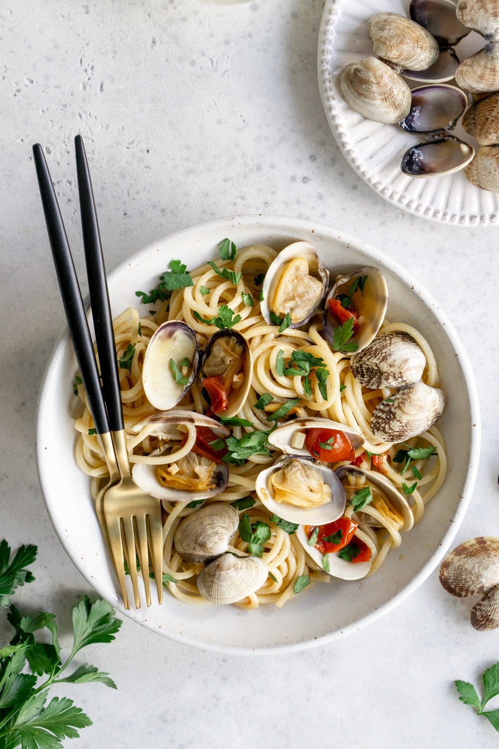 Clam pasta in a bowl with two forks, with a buncb of parsley to the left