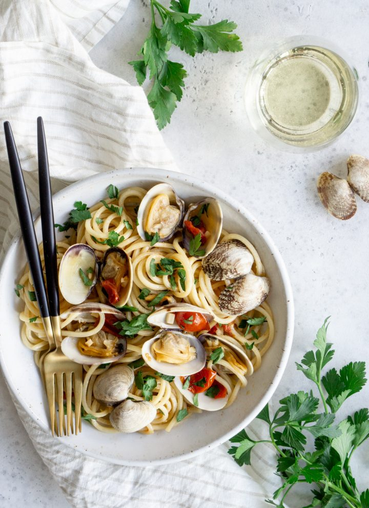 Bowl of clam pasta on a white napkin, surrounded by bunches of parsley