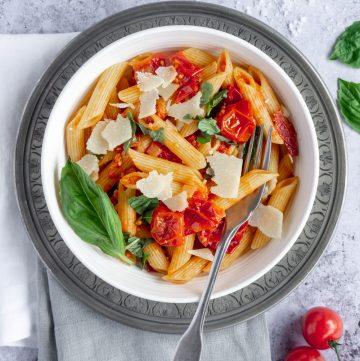 Bowl of pasta pomodoro sitting on top of two folded napkins