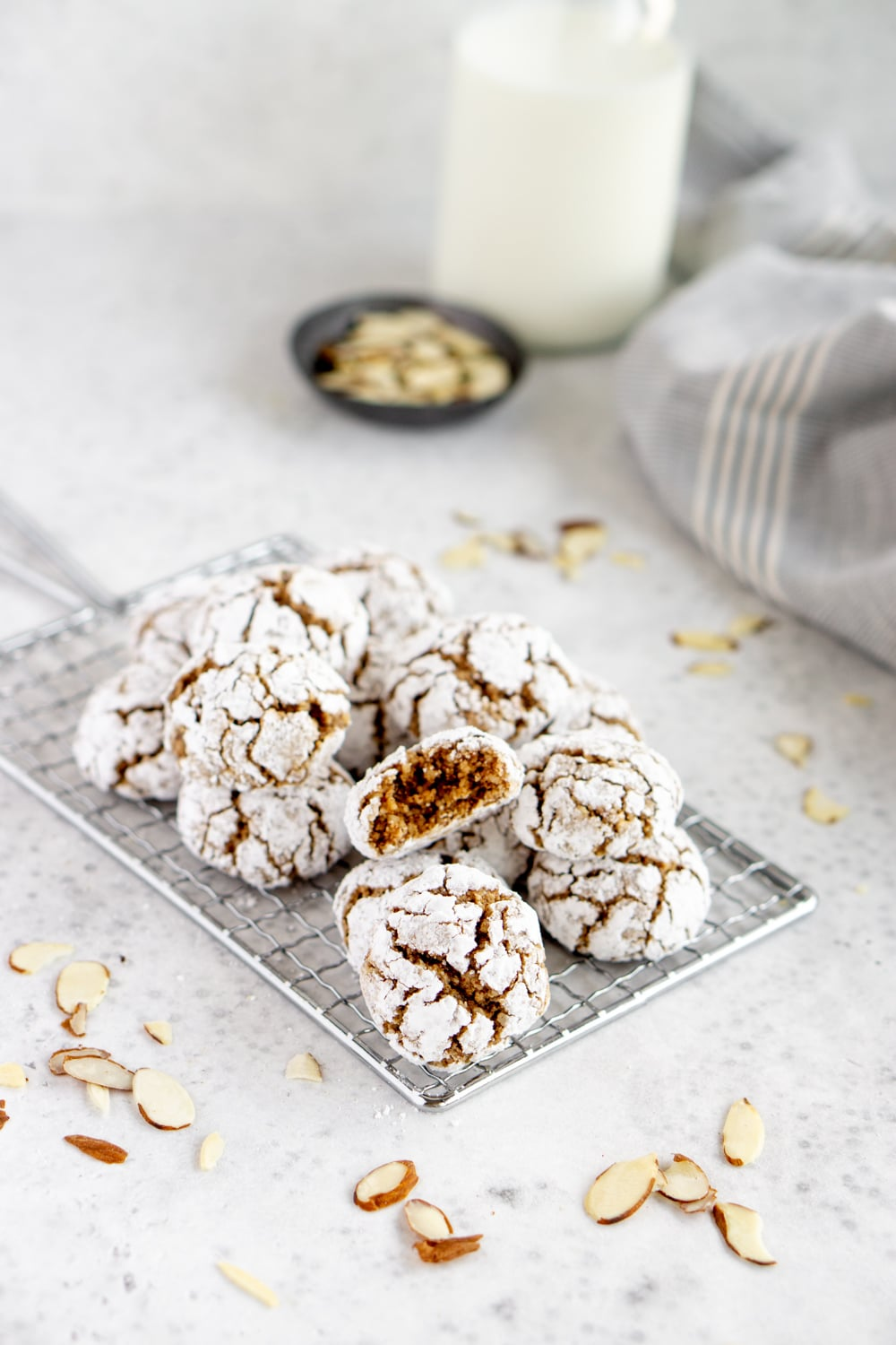 Amaretti cookies on a cookie sheet with milk and almonds in the background