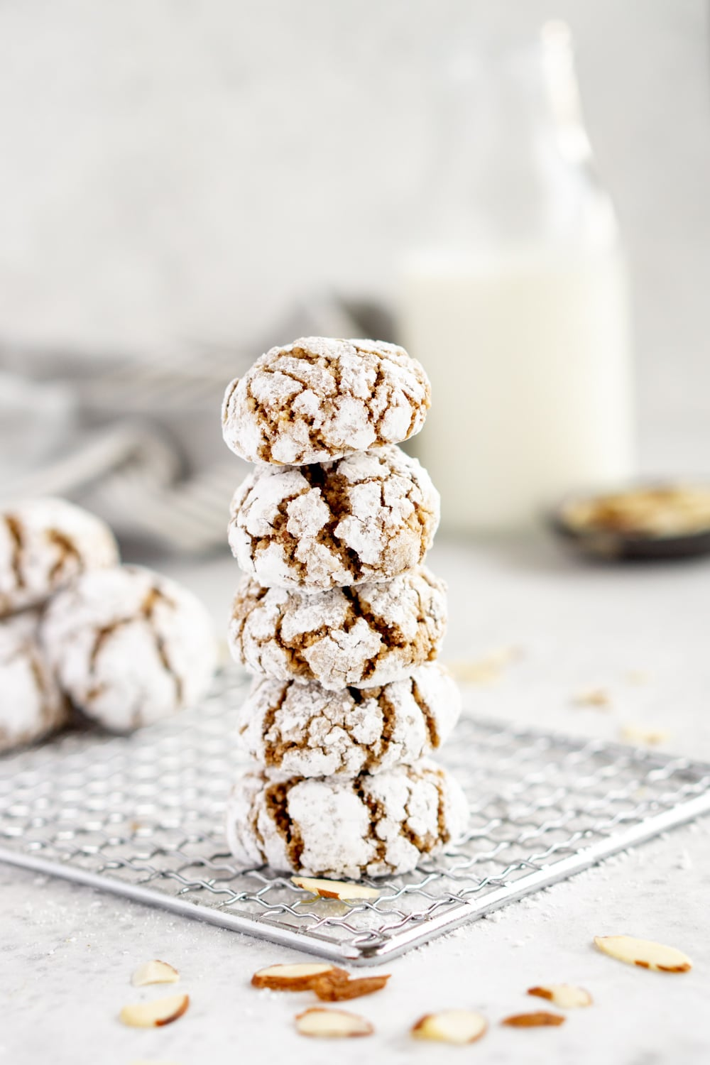 Stacked amaretti cookies on a baking sheet with milk in the background