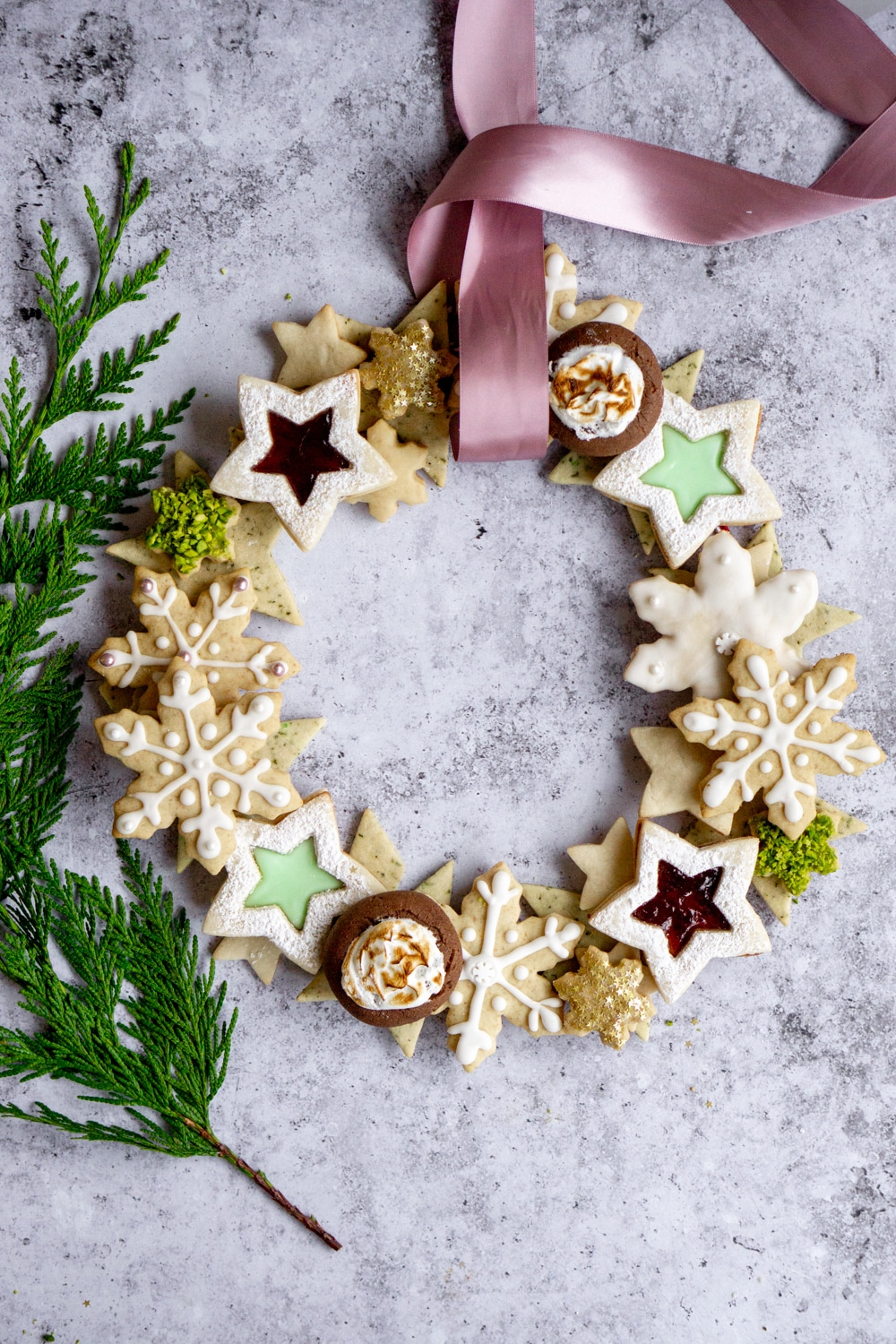 Overhead view of Christmas cookie wreath with holiday greens to the side