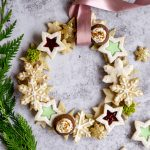 Holiday cookie wreath with greenery to one side and more cookies to the other side