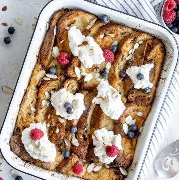 Panettone bread pudding in a baking dish topped with whipped cream and berries