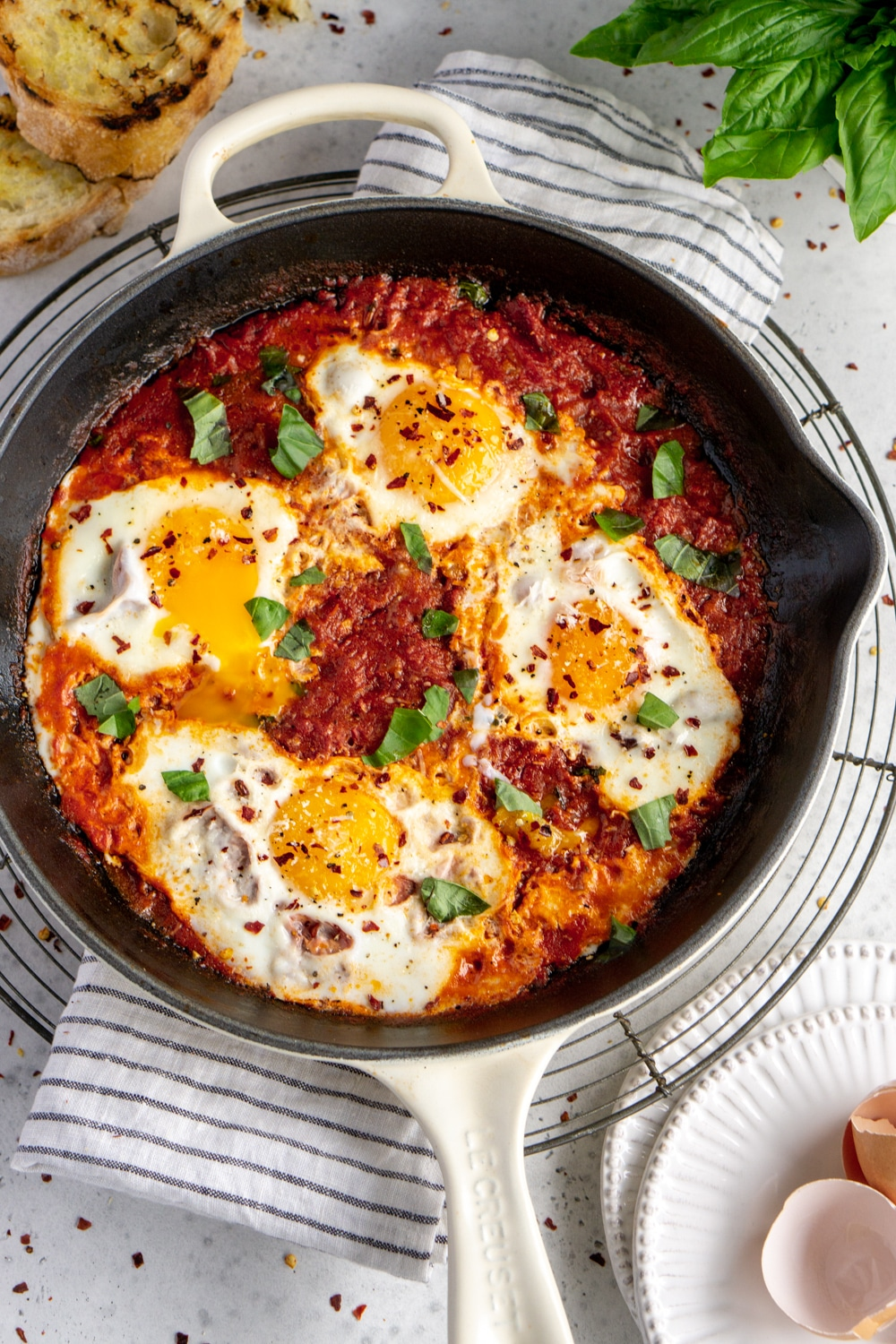 Eggs in tomato sauce in a pan topped with basil