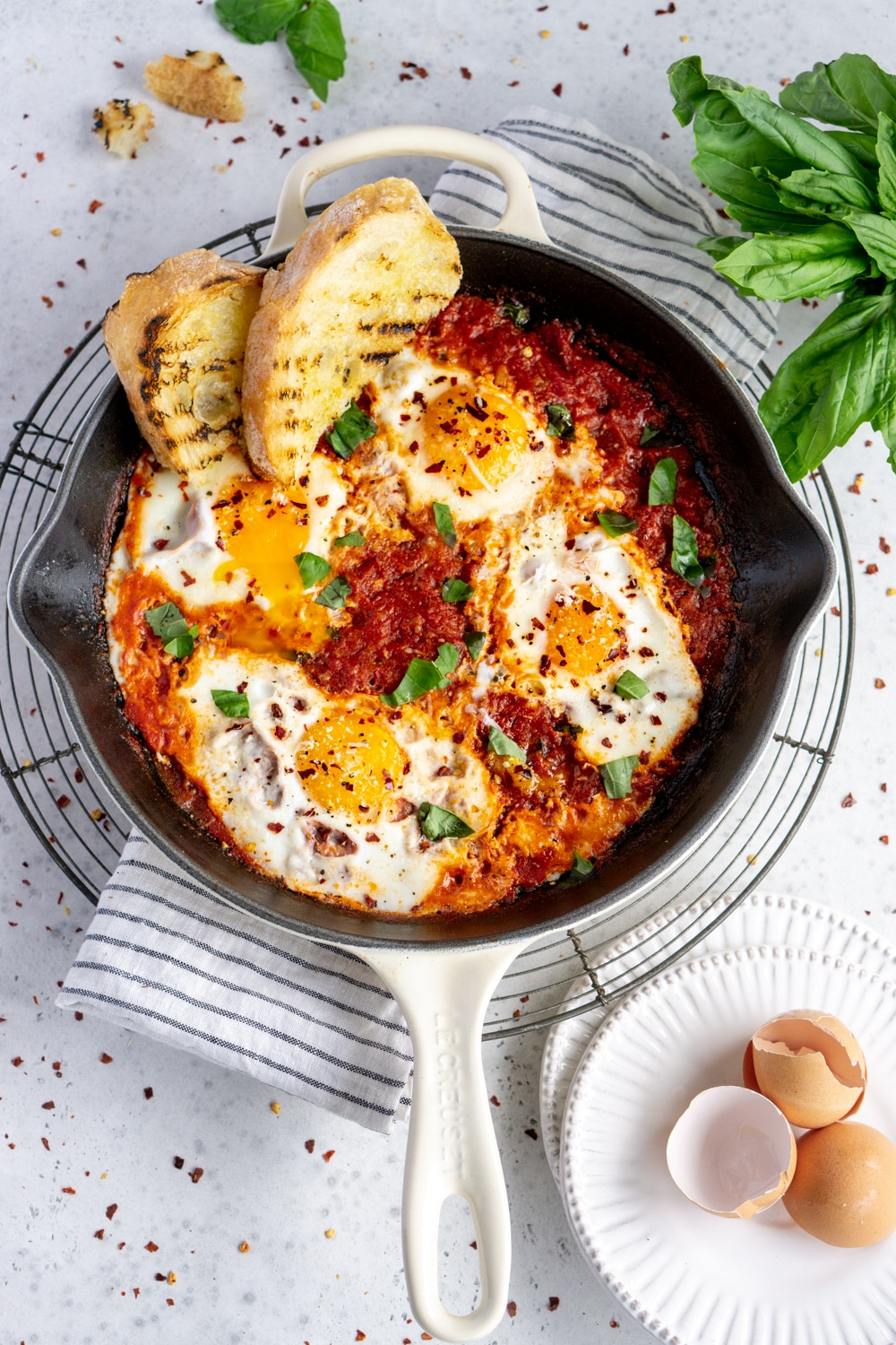 Eggs in purgatory in a white pan and grilled bread in the pan
