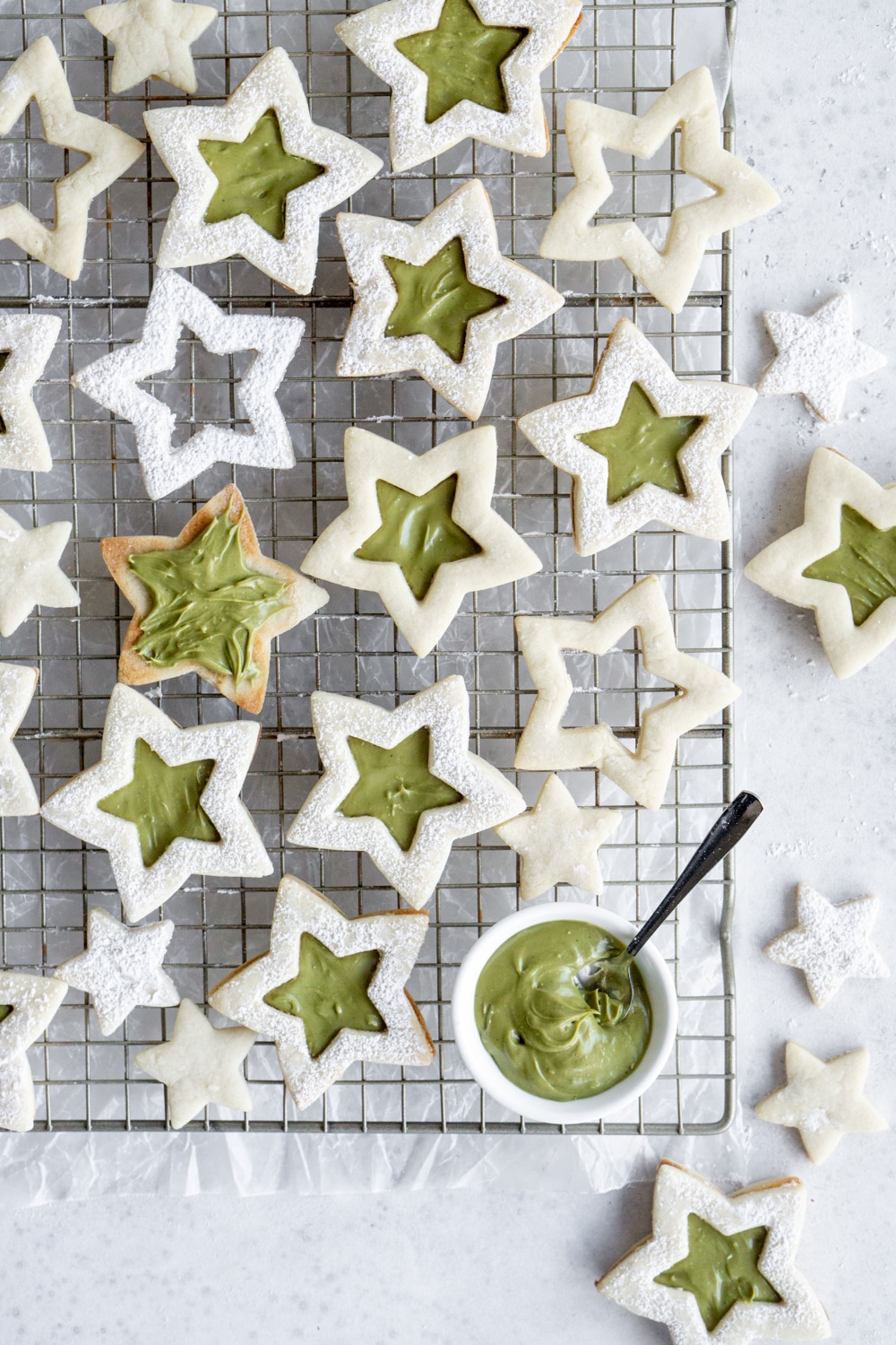 Star cookies on a cooling rack and a bowl of pistachio cream with a spoon