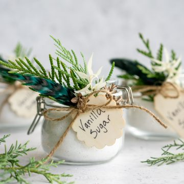 Three jars of vanilla sugar decorated with fresh greenery and tags