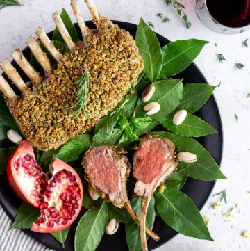 two lamb chops on a plate with a whole rack of lamb on a bed of bay leaves