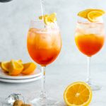 2 glasses of aperol spritz with prosecco being poured into one glass