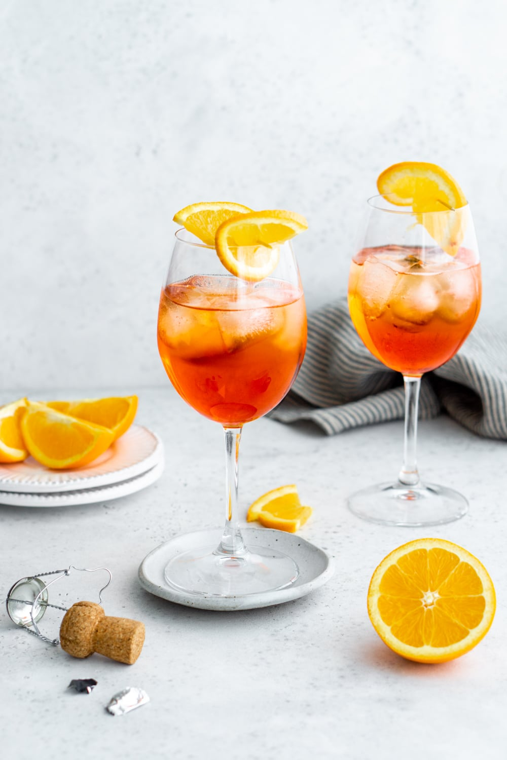 2 glasses of aperol spritz with oranges in the background