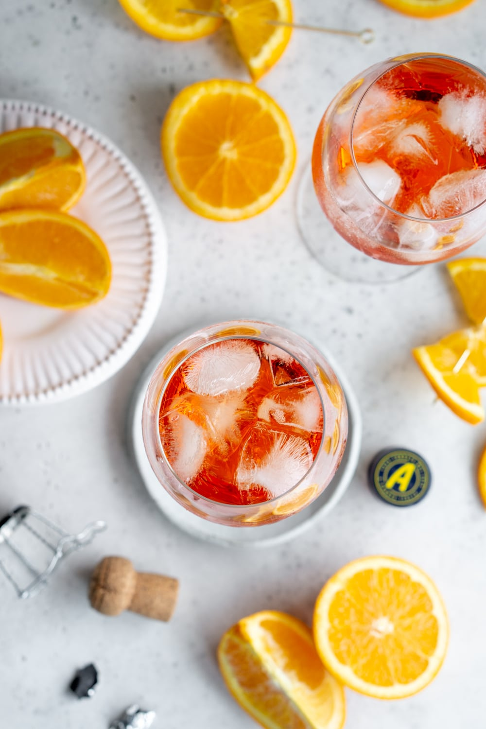 Overhead shot of 2 aperol spritz glasses with oranges scattered around
