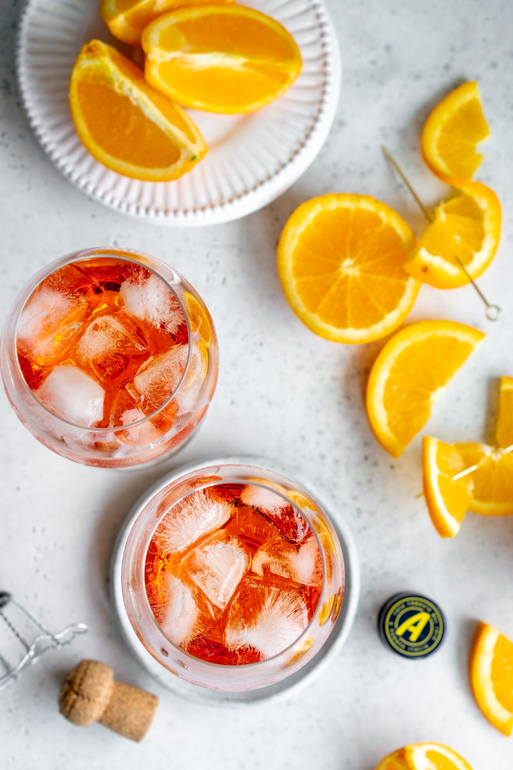 2 aperol spritz glasses with fresh oranges beside them
