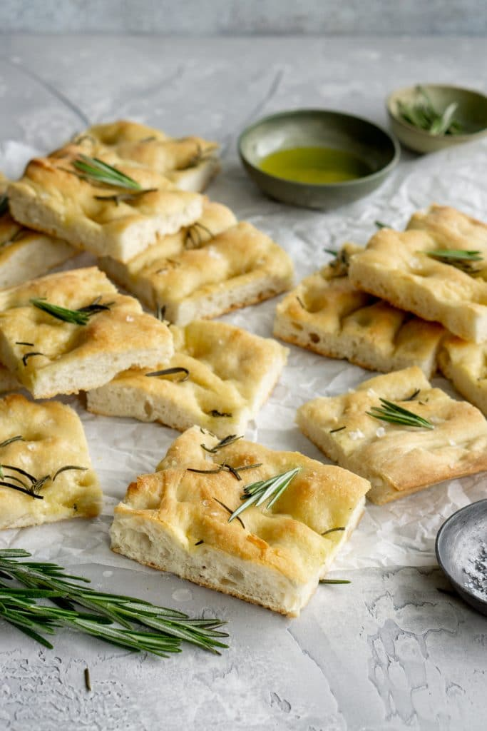 Pies of focaccia pizza on parchment paper with a bowl of olive oil in the background