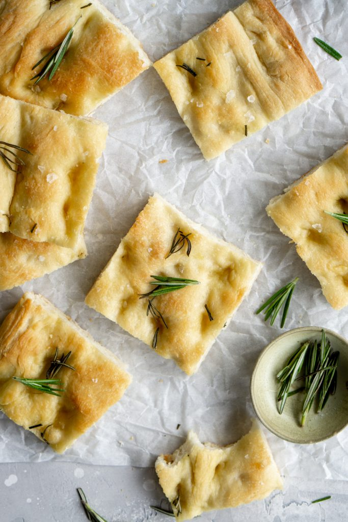 Square pieces of focaccia pizza topped with rosemary on parchment paper