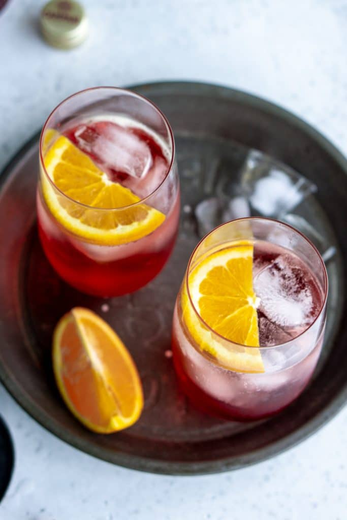 2 glasses of campari and soda garnished with orange slices in a circular steel dish