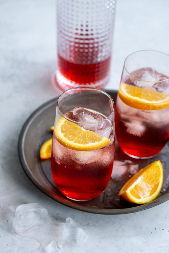 Campari and soda in a tall glass garnished with orange slices and a bottle of campari in the background