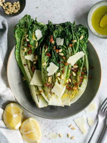 Grilled romaine salad in a bowl surrounded by lemons. pine nuts and vinaigrette