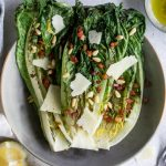 Overhead photo of grilled romaine salad topped with pancetta, pecorino and pine nuts