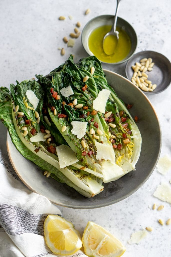 Grilled romaine salad with pine nuts and lemon vinaigrette in the background