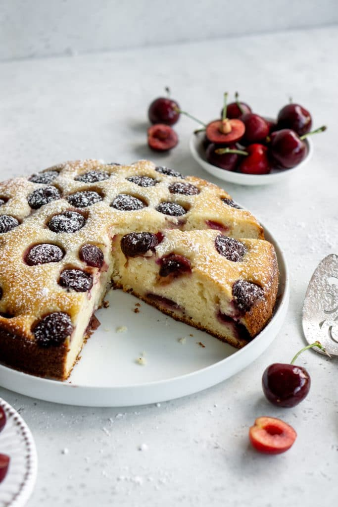Cherry cake cut into slices on a white plate with fresh cherries in the background