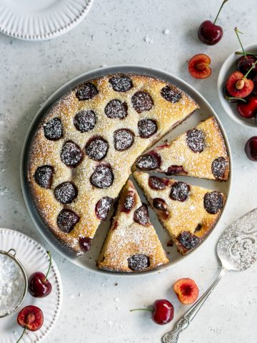 Cherry cake on a white plate with 3 slices cut out of it surrounded by fresh cherries