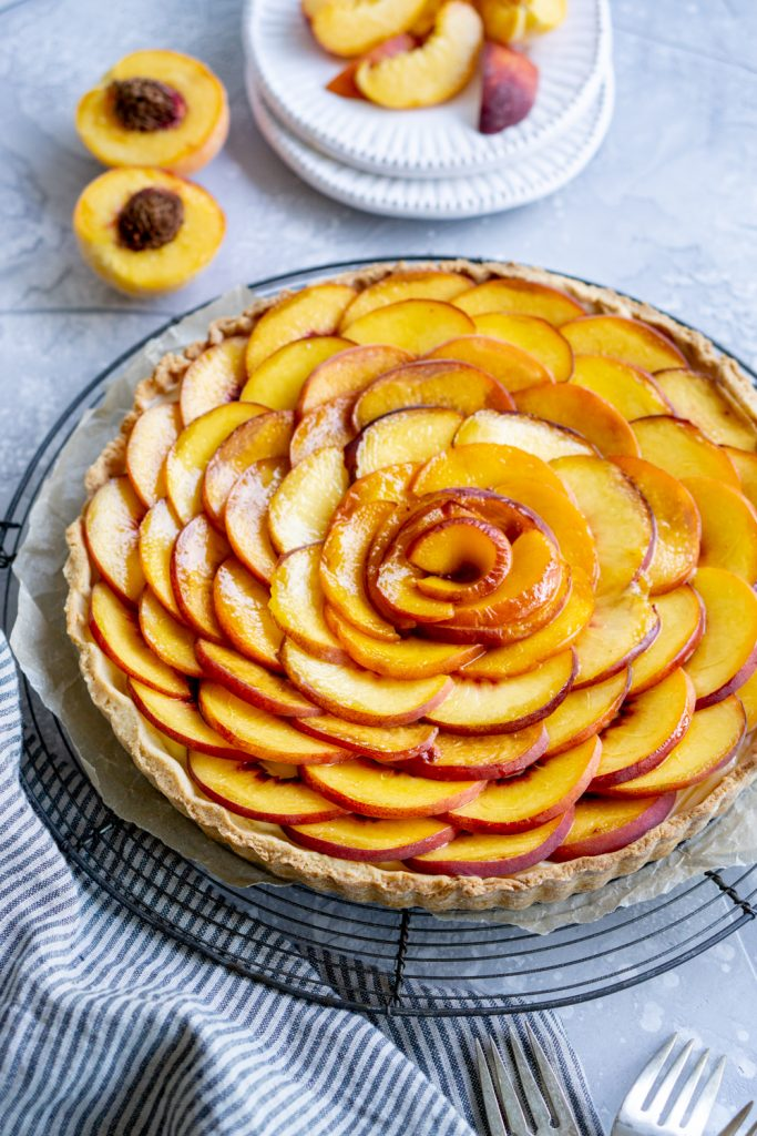 Side view of a peach tart with sliced peaches on a plate in the background