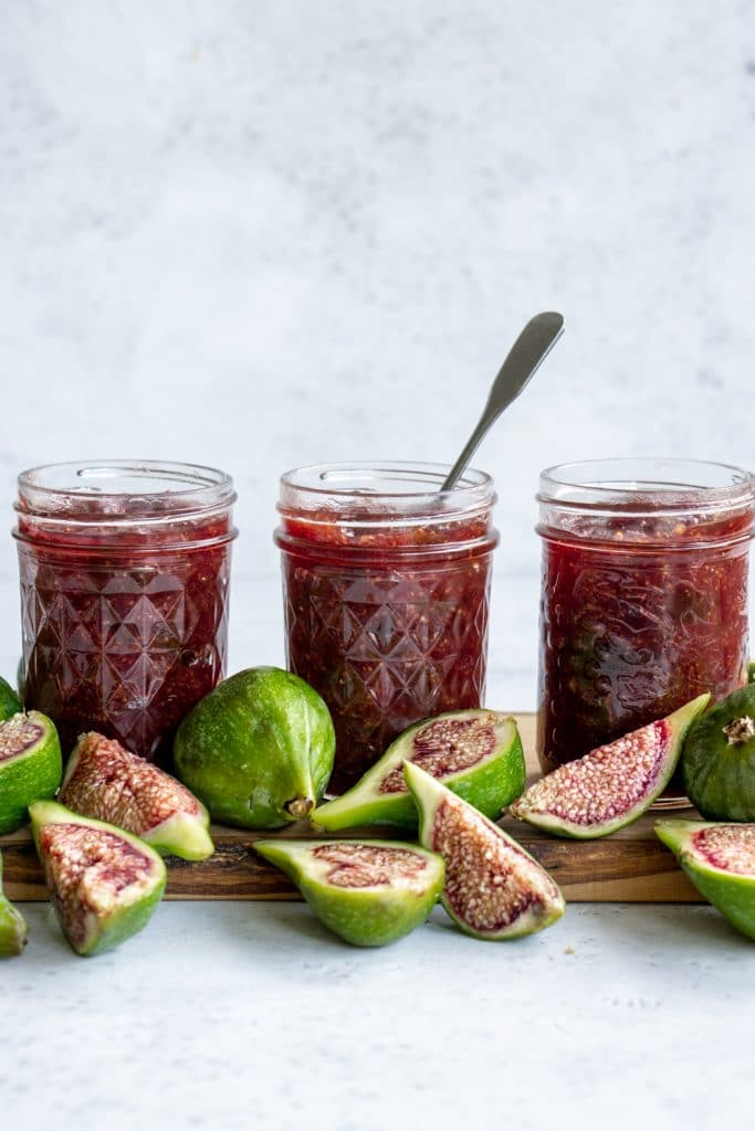 Three jars of fig jam on a wood board surrounded by fresh figs