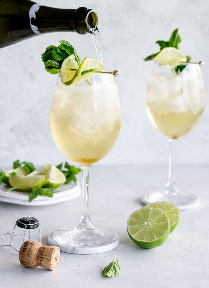 Prosecco being poured into a hugo cocktail with a fresh lime to the side