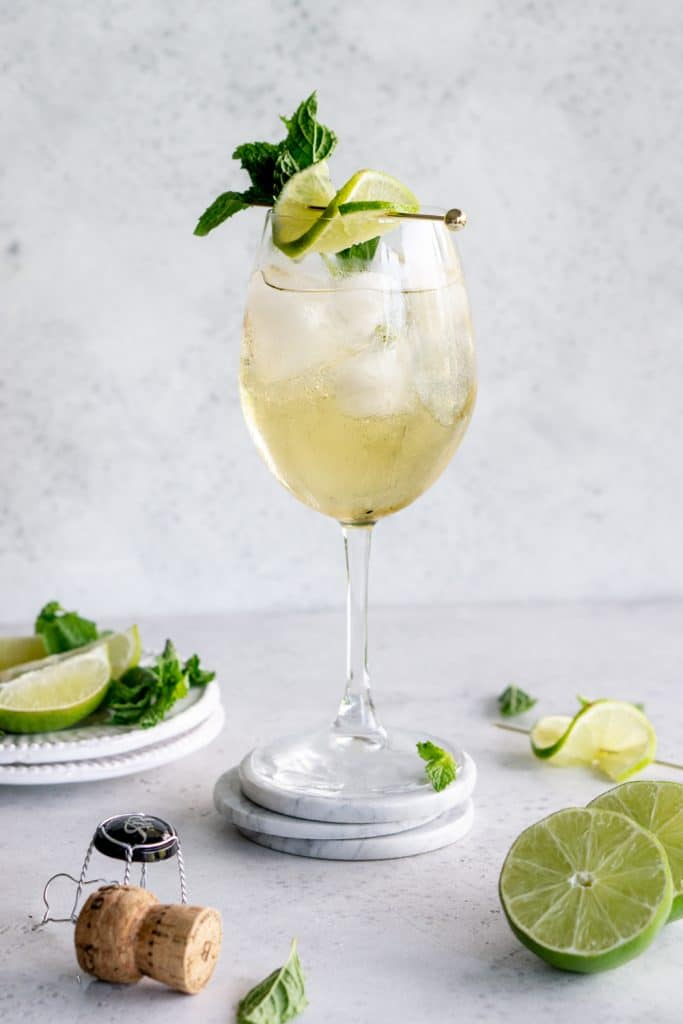 A hugo cocktail in a wine glass garnished with mint and lime