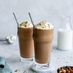 Two nutella milkshakes in tall glasses with a bowl of hazelnuts and a napkin to the side