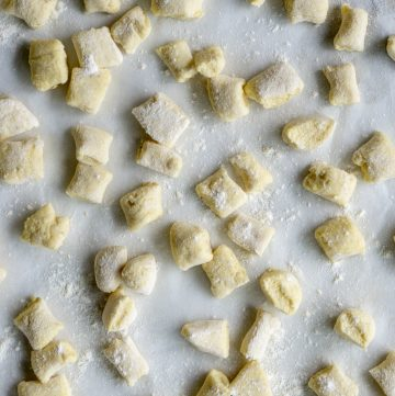 Uncooked ricotta gnocchi on a baking tray lightly dusted with flour
