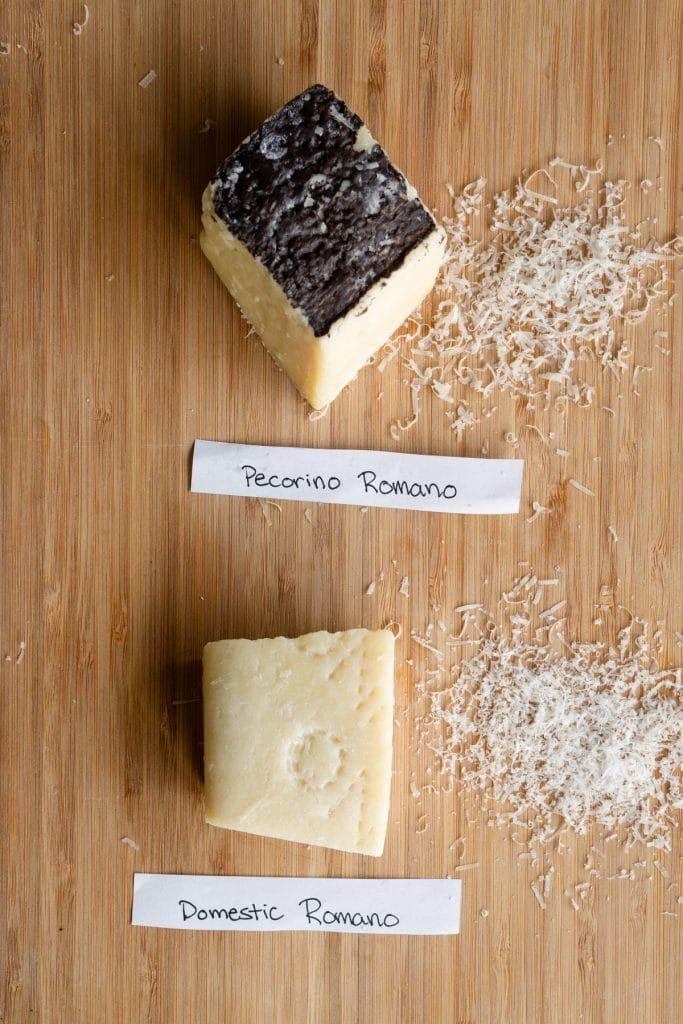 Pieces of pecorino romano and domestic romano on a wood board