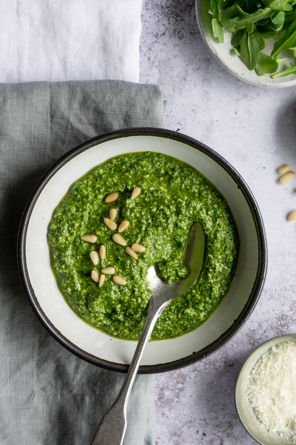 White bowl of arugula pesto topped with pine nuts, and a spoon in the bowl