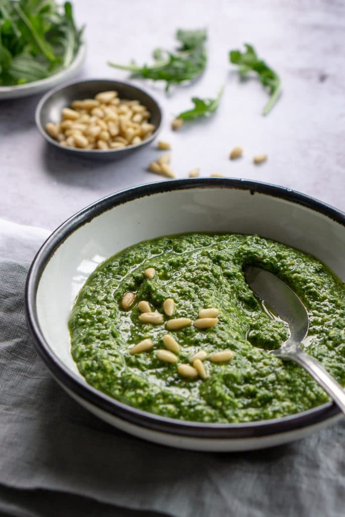 Side view of arugula pesto in a bowl with a dish of pine nuts and loose arugula in the background
