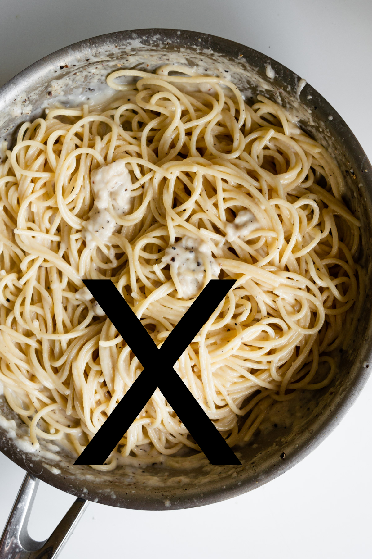 Pan of cacio e pepe with cheese that has clumped/curdled