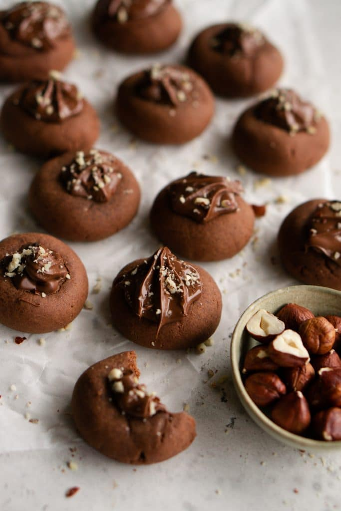 Cluster of 3-ingredient nutella cookies with a bowl of hazelnuts to the side
