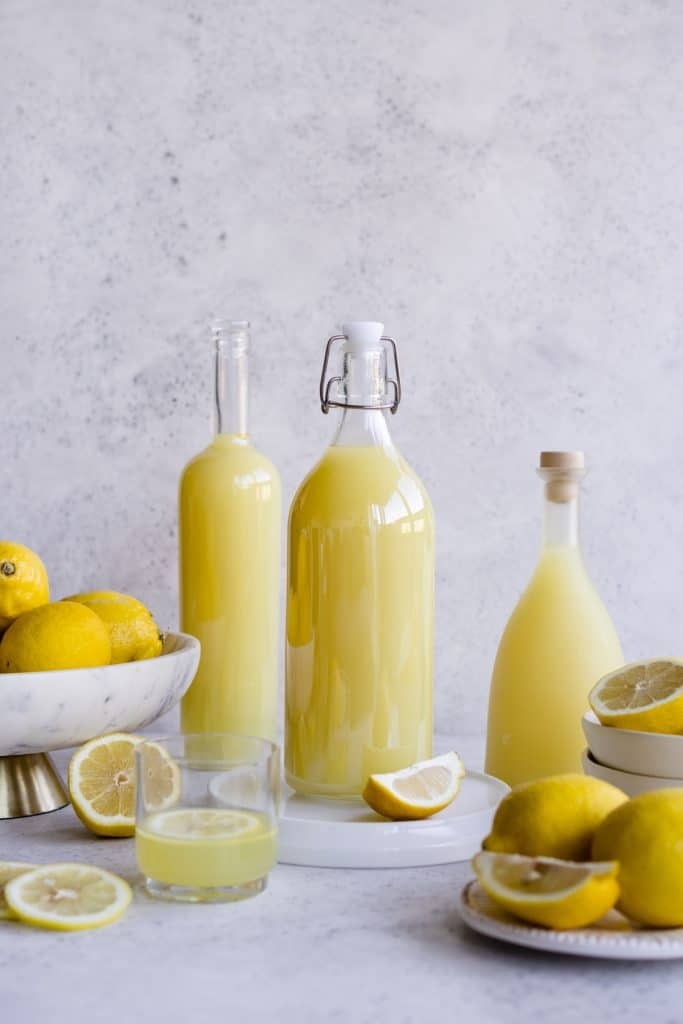 Three bottles of limoncello surrounded by bowls and plated of lemons