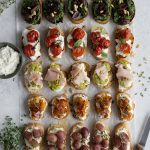 Five different types of crostini arranged on parchment paper with a knife and bowl of ricotta on either side