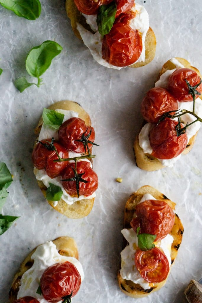 Five roasted tomato crostini on parchment paper with fresh basil to the side