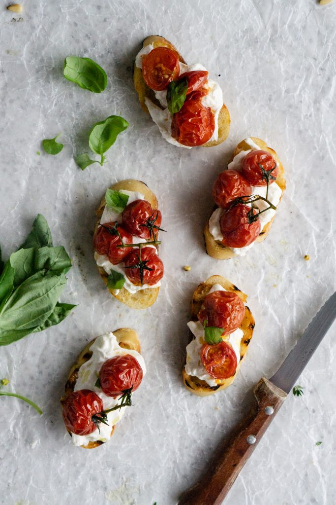 Roasted tomato crostini topped with fresh basil and a knife to the side