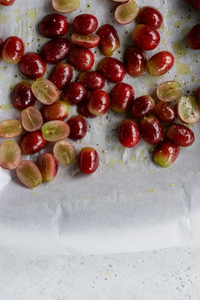 Fresh grapes cut in half on a baking sheet drizzled with olive oil, salt and pepper
