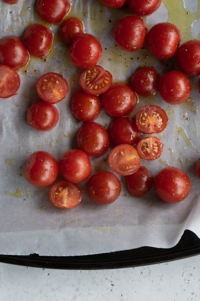 Raw tomatoes on a baking sheet drizzled with olive oil, salt and pepper