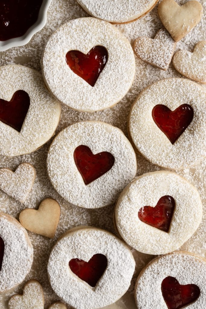 Overhead view of jam cookies with a heart cutout on parchment paper