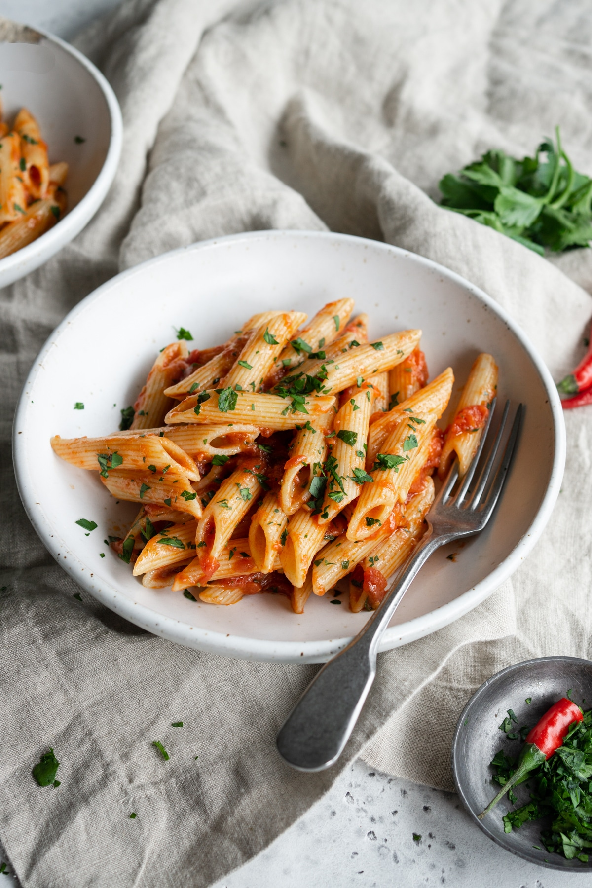 Bowl of penne arrabbiata on a linen napkin with parsley in the background