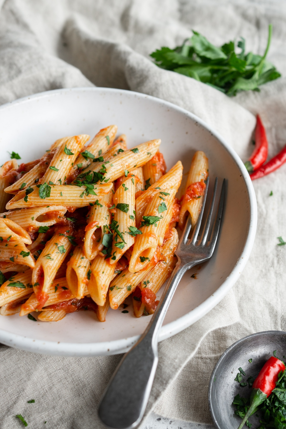 Penne arrabbiata in a bowl with a fork and chili peppers in the background