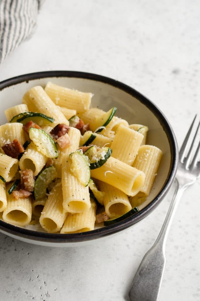 Zucchini and pancetta pasta in a white bowl